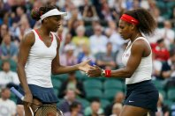 Serena Williams of the U.S. confers with her sister, Venus Williams (L), in the women's doubles tennis gold medal match against Czech Republic's Andrea Hlavackova and Lucie Hradecka at the London Olympic Games, August 5, 2012. REUTERS/Stefan Wermuth (BRITAIN - Tags: OLYMPICS SPORT TENNIS)